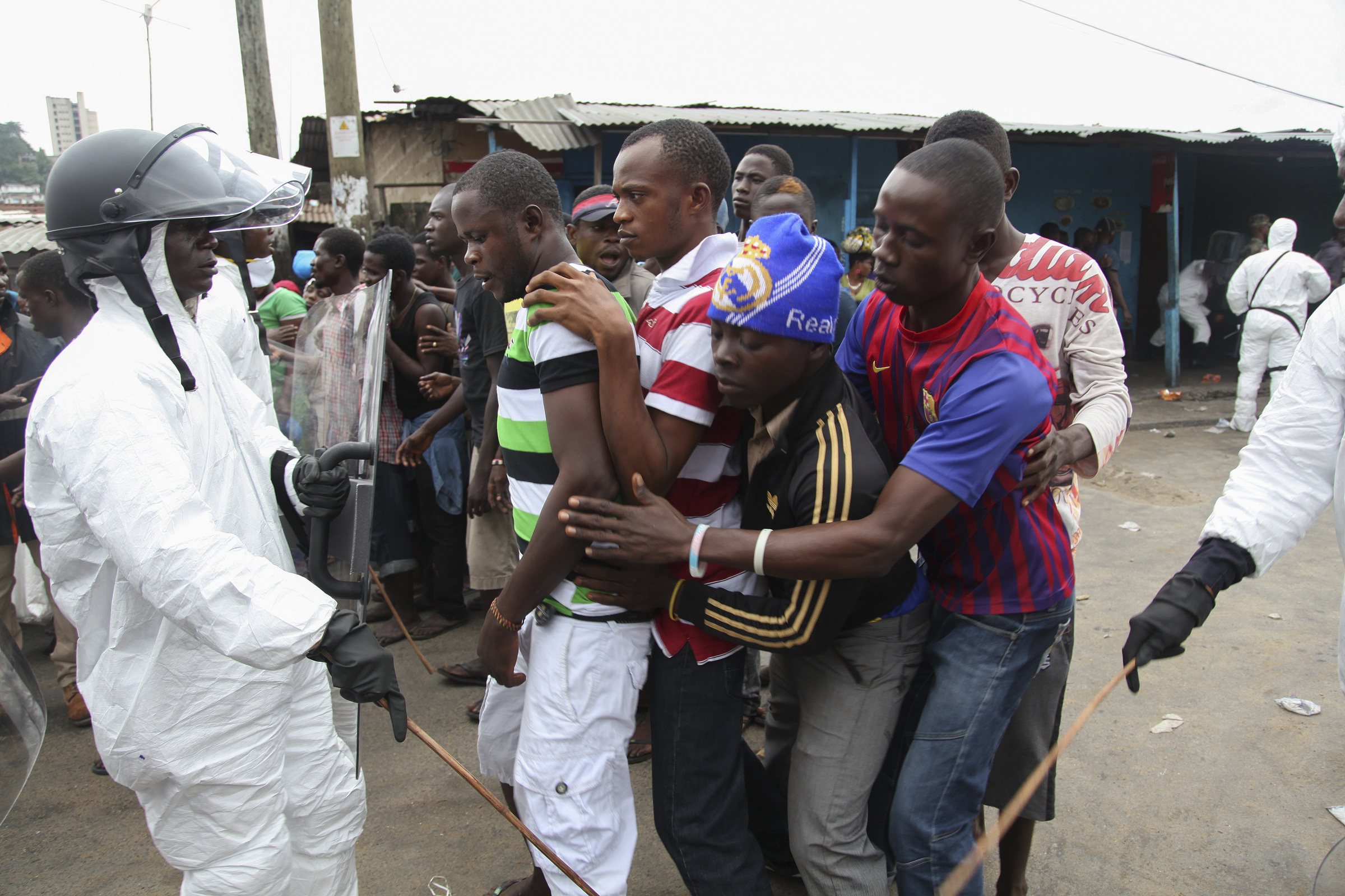 Liberian police control residents in Ebola quarantined area as they wait for food rations