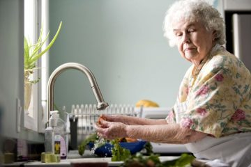 old-woman-in-kitchen-pictured-while-washing-carrots-and-radishes-725x483